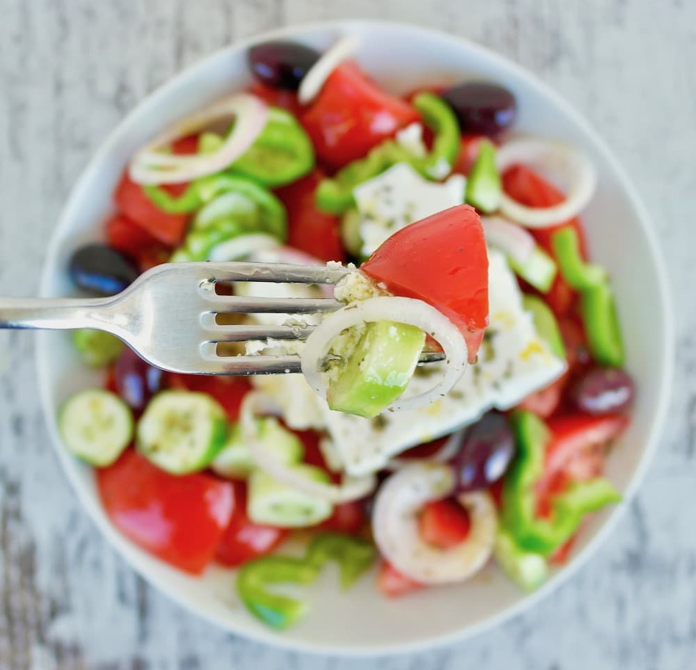 A traditional Greek salad made with tomatoes, cucumbers, olives, pepper, onion and feta in a white bowl.