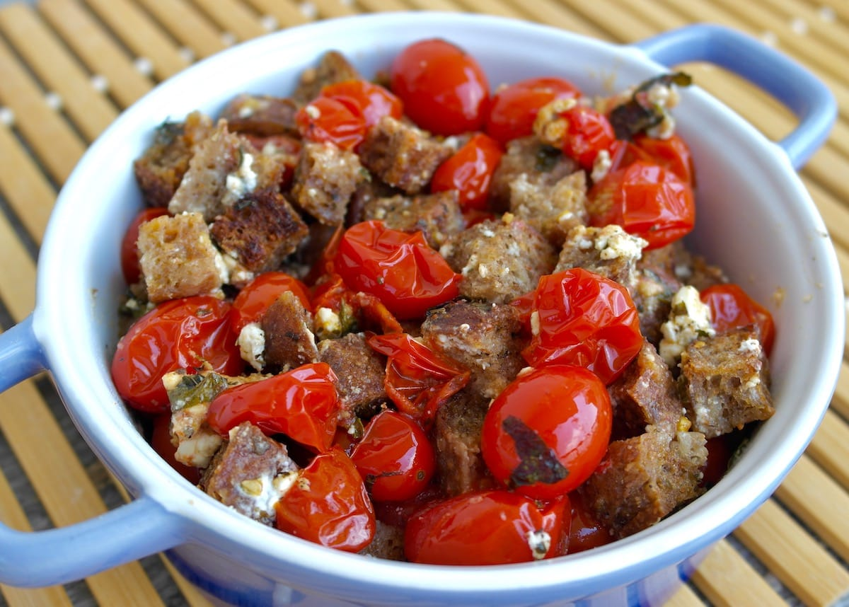 Roasted Cherry Tomatoes with Feta Cheese and Crunchy Croutons in a serving dish